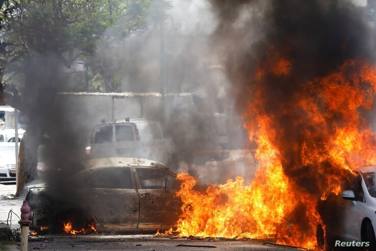 Cars go up in flames after a rocket launched from the Gaza Strip landed nearby, in Ashkelon, southern Israel, May 11, 2021.